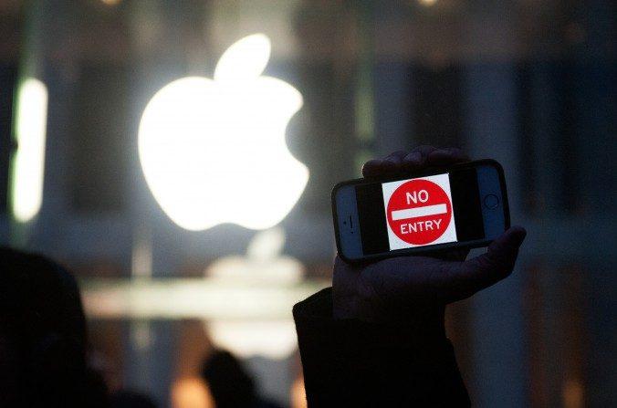 """Un detractor sostiene un iPhone que lee: """"Prohibdo el Paso"""" fuera de la tienda de Apple el 23 de febrero en la 5ta Avenida, ciudad de Nueva York. Mientras Apple afirma apoyar la privacidad de los usuarios, ha cooperado de cerca con las autoridades de China. (Bryan Thomas/Getty Images)"""