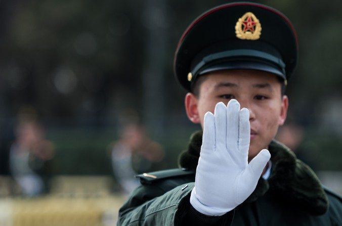 Un guardia de seguridad hace gestos fuera del Gran Salón del Pueblo en Beijing durante el segundo día del Congreso Nacional del Pueblo el 6 de marzo. El régimen chino recientemente anunció su Asociación de Seguridad Cibernética China, la cual ayudará a empujar su agenda para gobernar la Internet a nivel global. (Johannes Eisele / AFP / Getty Images)