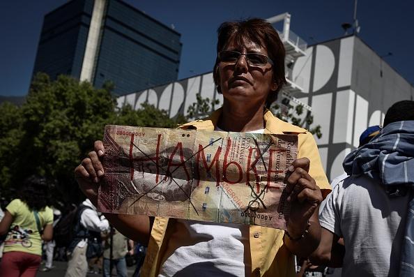 Un manifestante sostiene un gigante de cien bolívares, se nota con la palabra 'Hambre' escrito en él durante un mitin de la oposición en Caracas el 23 de enero de 2016. (Foto de Carlos Becerra/Agencia de Anadolu/Getty Images)