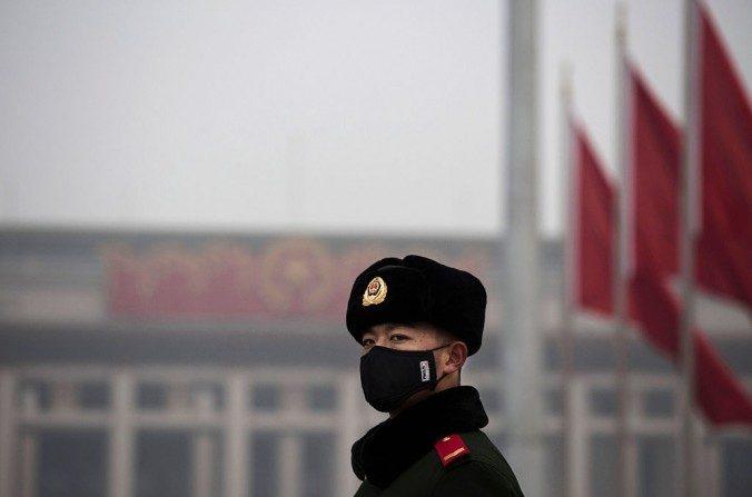 Un oficial de policía paramilitar chino lleva puesta una máscara para protegerse de la contaminación en la Plaza de Tiananmén el 9 de diciembre de 2015 en Beijing, China. (Kevin Frayer/Getty Images)