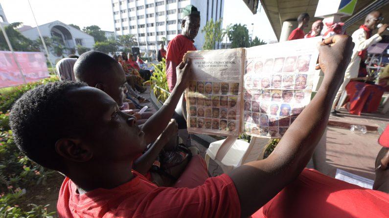 Un hombre mira las imágenes de niñas desaparecidas publicada en un diario local para marcar el segundo aniversario de los 219 escolares Chibok secuestrados por Boko Haram islamistas durante una manifestación en Lagos, el 13 de abril de 2016.combatientes islamistas secuestraron a 276 niñas de sus dormitorios en la noche del 14 de abril de 2014. Cincuenta y siete logró escapar en las horas que siguieron, pero que aún permanecen 219. En otras partes de Nigeria, marchas de protesta fueron planeadas como la culminación de una serie de una semana de eventos organizados por el movimiento #BringBackOurGirls renovar pide la liberación de las niñas (Photo credit should read PIO Utomi EKPEI / AFP / Getty Images)