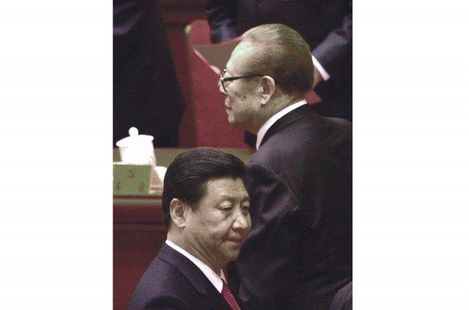 El ex líderchino Jiang Zemin (derecha) pasa cerca de Xi Jinping (izquierda) después de la clausura del 18º Congreso del Partido Comunista en el Gran Salón del Pueblo en Beijing el 14 de noviembre de 2012. (Wang Zhao / AFP / Getty Images)