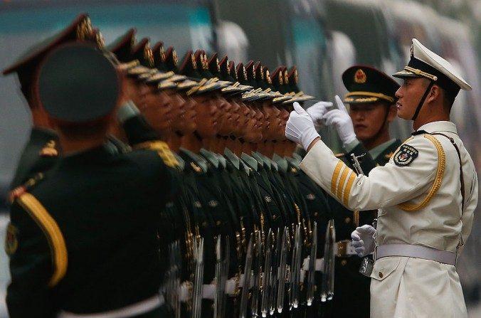 Soldados chinos de pie para una inspección en Beijing el22 de septiembrede 2013. El régimen chino comenzó el desmantelamiento de empresas comerciales manejadas por sus fuerzas armadas. (Lintao Zhang / Getty Images)
