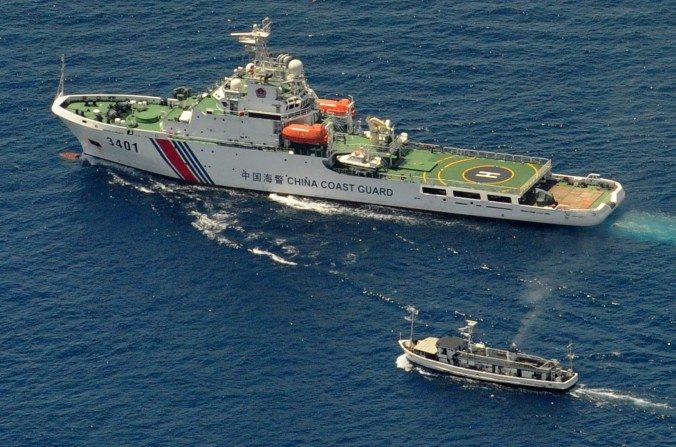 Un buque de la guardia costera china (parte superior) y un barco de suministro de Filipinas guardaron sus distancias en el momento que el barco filipino intentaba llegar al Banco de Arena Ayungin, un arrecife reclamado por ambos países en el Mar de China Meridional, el 29 de marzo de 2014. (Jay DirectoJ / AFP / Getty Images)