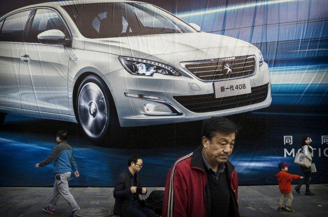 Chinos pasan por delante de una publicidad de un fabricante de autos extranjero en una pared el 27 de octubre de 2014 en Beijing, China. los líderes de la reforma económica de China afrontan varios obstáculos estructurales. (Kevin Frayer/Getty Images)