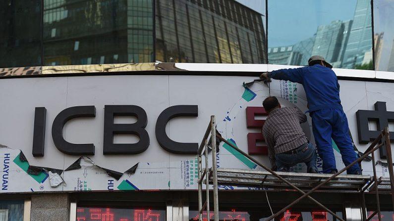 Trabajadores remodelando un cartel sobre la entrada de una sucursal del Banco Industrial y Comercial de China (ICBC) en Beijing, 5 de mayo de  2015. (GREG BAKER / AFP / Getty Images)