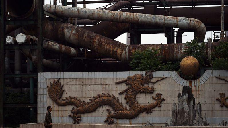 """Esta foto fue tomada el 28 de mayo del 2015. Muestra un trabajador que camina frente a una escultura de un dragón cerca de tuberías oxidadas de una planta de Hierro y Acero """"Shougang"""" en Beijing. (GREG BAKER / AFP / Getty Images)"""