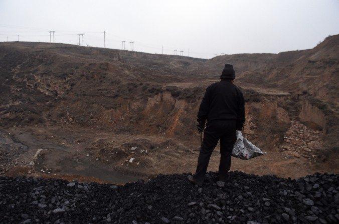 Una mujer parada en una pila de carbón cerca de una mina de carbón en Datong, en la provincia de Shanxi, el20 de noviembrede 2015. El carbón es uno de los sectores que está resultando difícil de reformar. (Greg Baker / AFP / Getty Images)