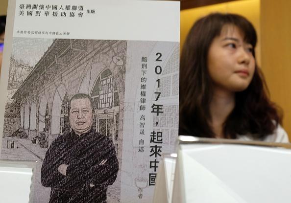 """Gracia Geng, la hija de uno de los abogados más prominentes de derechos humanos en China, Gao Zhisheng, sostiene un libro, titulado """"Stand Up China 2017 (China se levanta en el 2017) – La Esperanza China: Lo que aprendí durante cinco años como preso político"""", escrito por su padre, en una conferencia de prensa en Hong Kong, el martes 14 de junio del 2016.(Foto: SAM YEH/AFP/Getty Images)"""