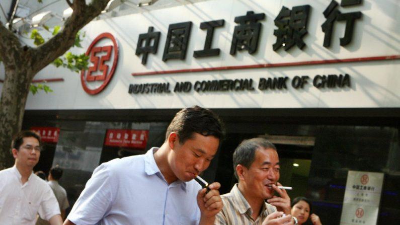 Un grupo de hombres chinos pasa junto a una sucursal del Banco Industrial y Comercial de China (ICBC) en Shanghai, 09 de octubre de 2006. (MARCA RALSTON / AFP / Getty Images)