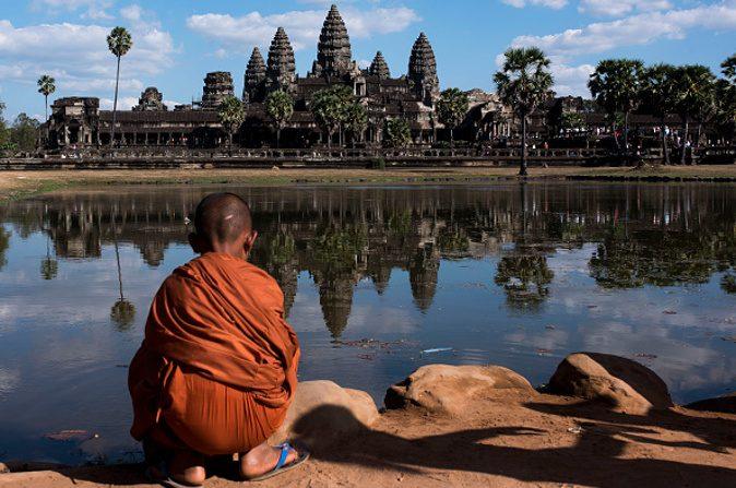 Un joven monje sentado frente al templo de Angkor Wat, el 01 de enero de 2016, en Siem Riep, Camboya. Angkor fue la ciudad capital del imperio jemer que floreció aproximadamente entre los siglos IX al XV. (Xaume Olleros/ Getty Imagenes)