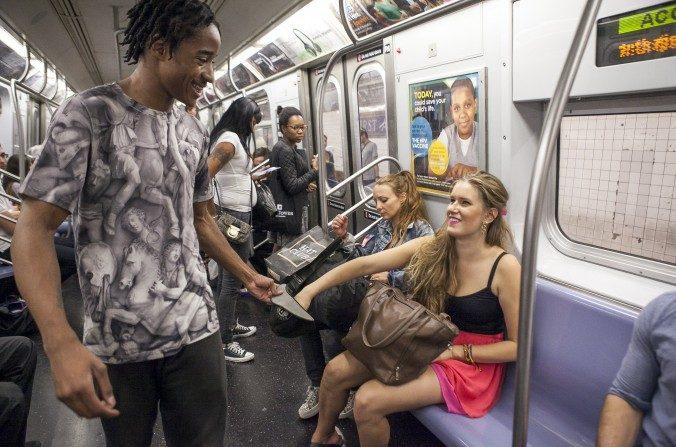 El acróbata Ainsley Brundage, recibe dinero después de su actuación en el metro de Nueva York. (Samira Bouaou/La Gran Época)