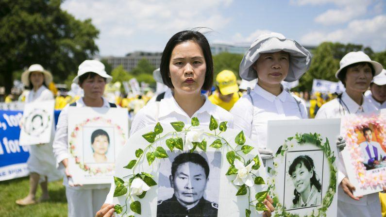 Jiang Li con una foto de su fallecido padre Jiang Xiqing, en un acto en Washington DC el 14 de julio de 2016 para pedir justicia. Su padre murió asesinado  por las autoridades comunistas en un campo de trabajo forzado por practicar la disciplina espiritual Falun Dafa. (Lisa Fan/La Gran Época)