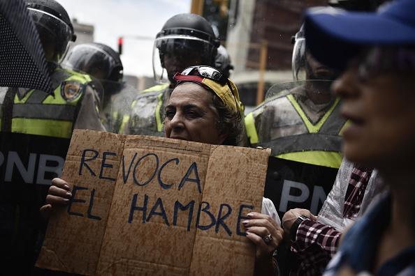 Un manifestante sostiene un letrero que dice 'Revocar el hambre' frente a la Policía Nacional venezolana (Fotógrafo: Carlos Becerra/Bloomberg a través de Getty Images)