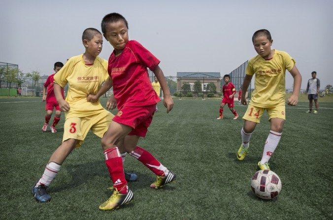 Niños jugando fútbol en una cancha de práctica en la Escuela de Fútbol Internacional Evergrande en la provincia de Guangdong, China. China proyecta la construcción de más de 20.000 escuelas de fútbol para elevar su posición internacional en este deporte. (Kevin Frayer / Getty Images)