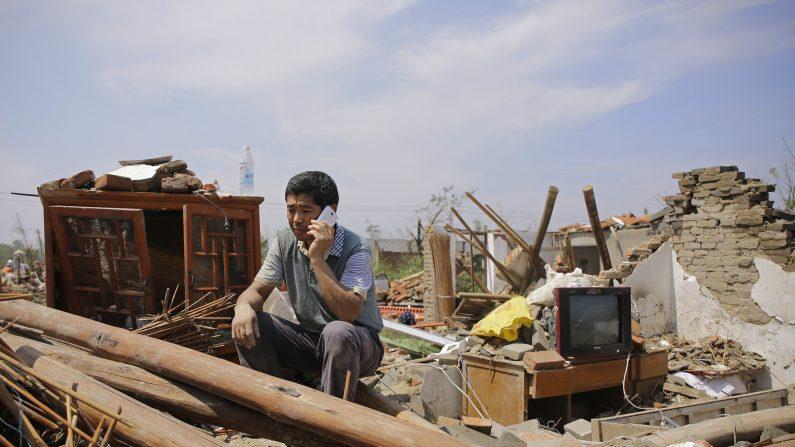 Una persona llama desde una casa colapsada en el pueblo Danping de la ciudad Yancheng, provincia de Jiangsu el 23 de junio de 2016. (Foto de Wang He/Getty Images)