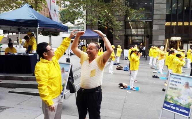 Un transeúnte se detiene para aprender los ejercicios de Falun Dafa durante la práctica de grupo en Australia en esta foto de archivo . ( Minghui.org )
