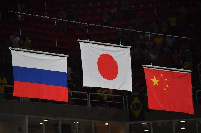 De izquierda a derecha: Las banderas de Rusia, Japón y china las cuales se muestran en el estadio Olímpico, después de la final masculina en gimnasia artística en los Juegos Olímpicos de Río, el 8 de agosto de 2016. (Ben STANSALL / AFP / GettyImages)