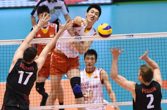 Geng Xin (# 11) de China golpea el balón por sobre Graham Vigrass (# 17) y John Perrin (# 2) de Canadá durante la clasificación final mundial en voleibol masculino de los Juegos Olímpicos para Río de Janeiro del 2016 en Tokio, el 5 de junio de 2016. (Toru Yamanaka / AFP / Getty Images)
