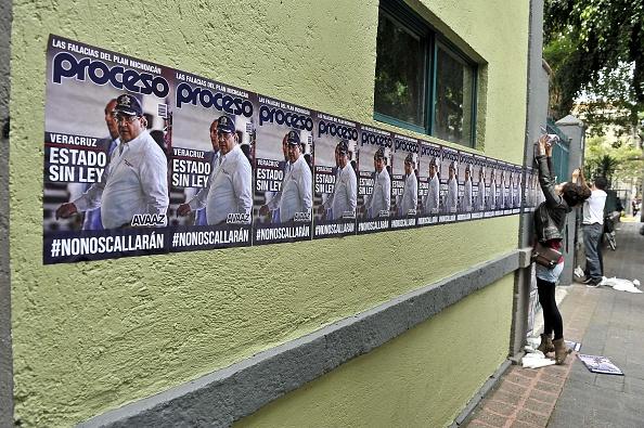 Activista empapelando la calle en una protesta contra gobernador de Veracruz Javier Duarte, en 2015.      (Photo credit should read YURI CORTEZ/AFP/Getty Images)