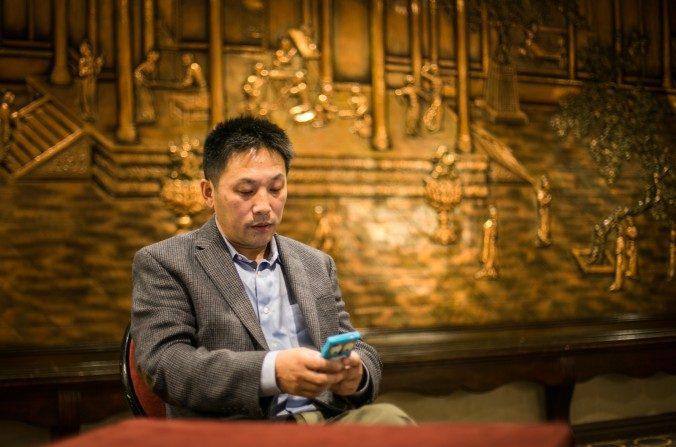 Li Hongkuan utiliza la aplicación WeChat, un medio de comunicación social, en Flushing, Nueva York, el 4 de octubre. WeChat ofrece la posibilidad a los activistas para difundir contenido más subversivo, pero con un público más limitado en China. (Matthew Robertson / La Gran Época)
