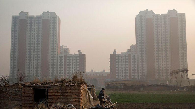 Una granjera mayor fuera de su granja con un nuevo emprendimiento inmobiliario en las afueras de Beijing, el 21 de noviembre de 2014. (Kevin Frayer/Getty Images)