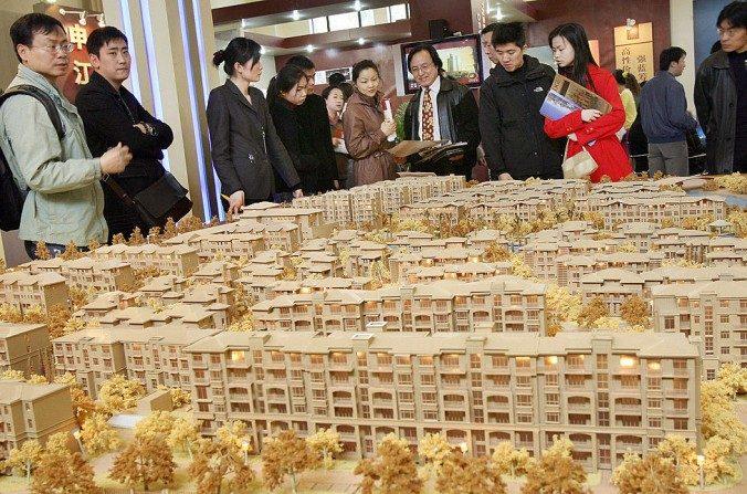 Un grupo de potenciales compradores de bienes raíces mira un plano inmobiliario de un constructor local en una exposición de bienes en Shanghai el 19 de marzo de 2006. (Marcos Ralston / AFP / Getty Images)