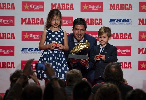 El delantero del Barcelona Luis Suárez (C) posa con sus hijos Delfina (Izq.) y Benjamin, luego de recibir el Balón de Oro 2015-2016. (JOSEP LAGO/AFP/Getty Images)