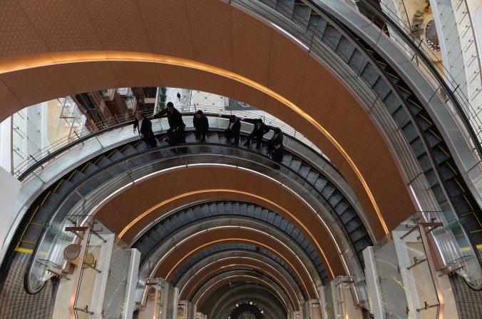 Clientes en un ascensor en forma de espiral dentro de un nuevo centro comercial abierto en Shanghai el 17 de Marzo de 2015. La inversión china en el extranjero parece estar disminuyendo con la economía en general. (STR / AFP / Getty Images)