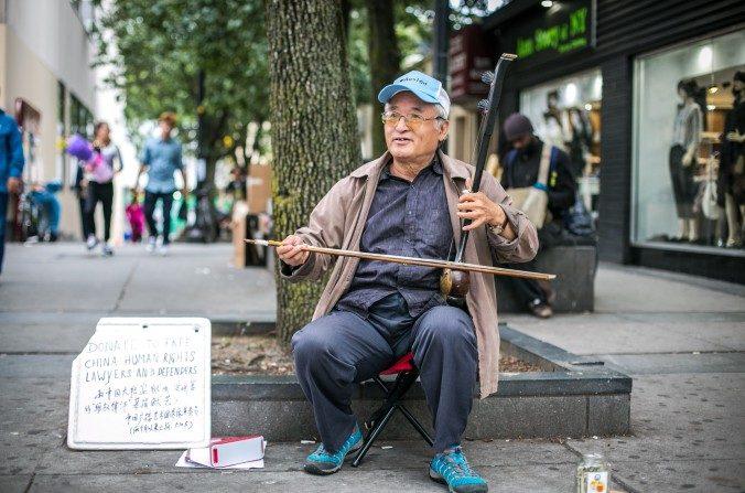 Xin Xiulu toca el erhu en Flushing, Nueva York y acepta donaciones a la gorra para los abogados de derechos humanos detenidos en China, el 29 de septiembre (Benjamin Chasteen/La Gran Época)