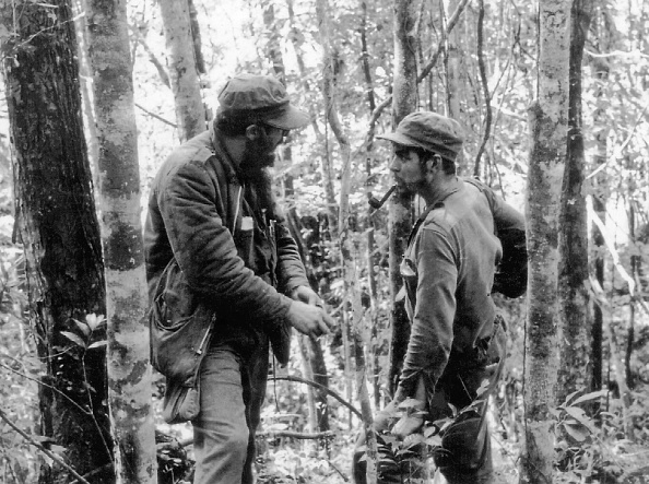 Foto del 8 de octubre de 1957 muestra al líder cubano Fidel Castro (Izq.) conversando con Ernesto 'Che' Guevara (Der.), en los bosques de la Sierra Maestra, Cuba. (ARCHIVOS / AFP / Getty Images)