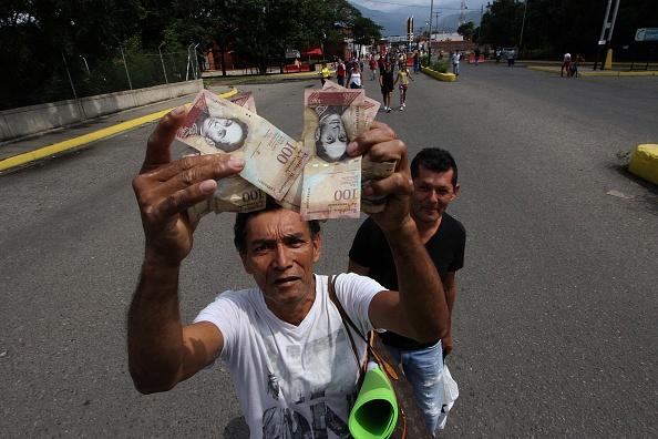 Un hombre muestra billetes de 100 bolívares en Venezuela. El domingo 11 de diciembre el presidente Nicolás Maduro ordenó que esos billetes no circularían más ya que denunció maniobras mafiosas detrás de su uso. ( GEORGE CASTELLANOS/AFP/Getty Images)