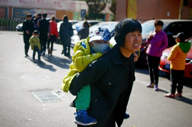 Una mujer lleva a un niño en su espalda en Beijing el 24 de noviembre de 2014. (Wang Zhao / AFP / Getty Images)