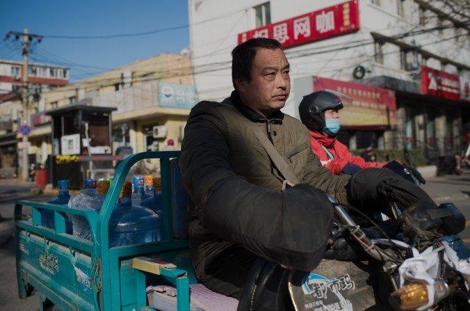 Un trabajador con contenedores de agua conduce en una calle de Beijing el 9 de diciembre de 2016. El economista Ma Guangyuan dice que China necesita desarrollar auténticos derechos en la propiedad para mejorar el crecimiento económico. (Nicolas Asfouri / AFP / Getty Images)