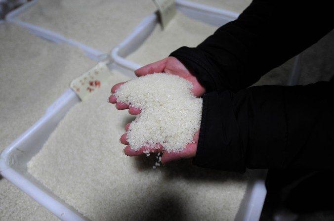 Un vendedor coge el arroz en su puesto en un mercado en Beijing el 2 de diciembre de 2009. (Peter Parks / Getty Images)