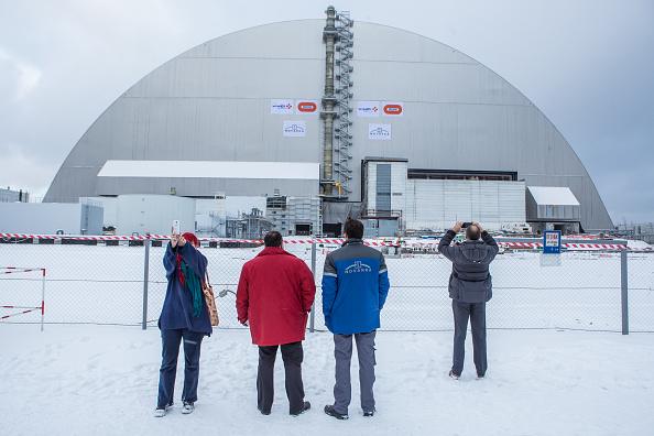 Personas toman fotos después de un acto para marcar el movimiento del sarcófago nuevo de seguridad sobre el reactor 4 en la central nuclear de Chernóbyl, el 29 de noviembre de 2016 en Chernobyl, Ucrania. (Brendan Hoffman / Getty Images)