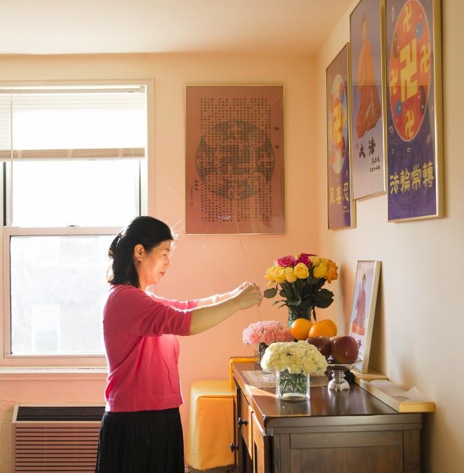 Wang Huijuan brinda sus respetos al fundador de Falun Gong en su casa en Queens, New York, el 8 de Enero del 2017. Con su esposo y su hija, escaparon de China en el 2014 y encontraron asilo luego de años de tortura por practicar Falun Gong. (Samira Bouaou/La Gran Época)