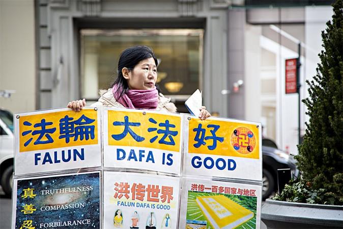 Wang Huijuan, en frente del Empire State en Manhattan, New York, el 12 de Enero del 2017, sostiene un aviso para ayudar a los turistas chinos a entender los hechos acerca de la persecución de Falun Gong en China. (Samira Bouaou/La Gran Época)