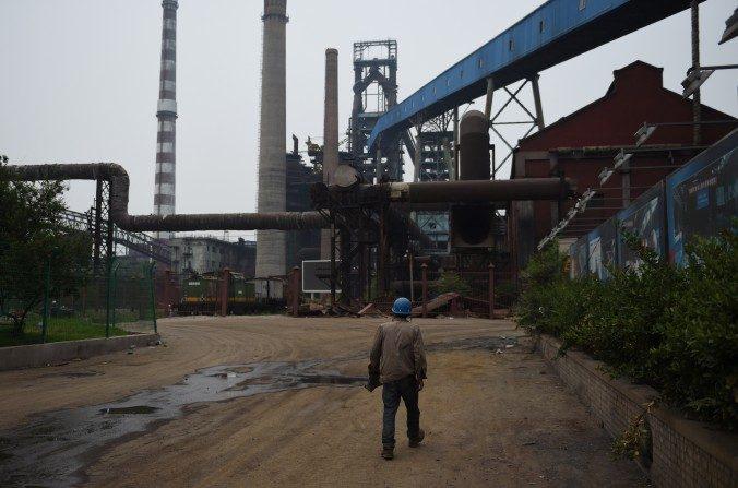Esta foto tomada el 28 de mayo de 2015 muestra un trabajador en demoliciones que camina cerca de edificios abandonados en la planta de hierro y acero de Shougang capital en Beijing. El erudito chino Liu Shijin dice que la economía de China está decayendo. (Greg Baker / AFP / Getty Images)