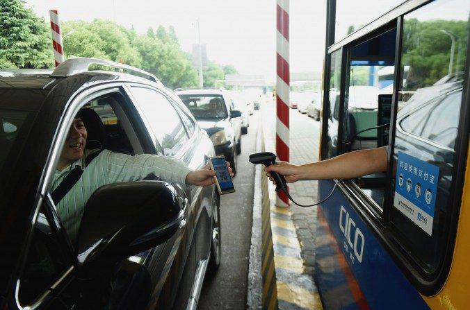 Un conductor usa su teléfono inteligente para pagar el peaje de la autopista usando Alipay, una aplicación del servicio de pago en línea de Alibaba, en una estación de peaje en la autopista Hangzhou-Ningbo en Hangzhou, China. (STR / AFP / Getty Images)