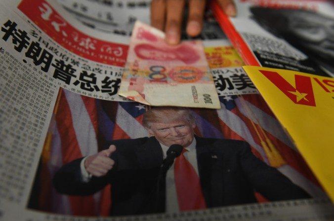 Un billete de 100 yuanes es puesto sobre un periódico con  la foto del presidente electo de EE. UU. Donald Trump en un puesto de periódicos en Beijing el 10 de noviembre de 2016.  (Greg Baker/AFP/Getty Images)