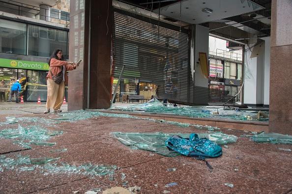 Una mujer toma una foto de una premisa de negocios muy dañada frente a la Plaza Independencia en Montevideo el 3 de enero de 2017. (Foto: PABLO PORCIUNCULA/AFP/Getty Images)
