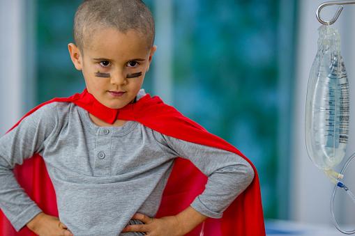 Un niño pequeño con el cáncer lleva pintura de guerra y una capa súper héroe mientras recibe su tratamiento de quimioterapia. (FatCamera)