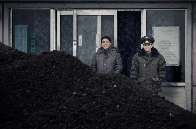 Un oficial militar de Corea del Norte (derecha) y un hombre de este mismo país (izquierda) de pie detrás de un montón de carbón a lo largo de las orillas del río Yalu en el noreste del pueblo fronterizo norcoreana de Siniuju, el 14 de diciembre de 2012. (Wang Zhao / AFP / Getty Images)