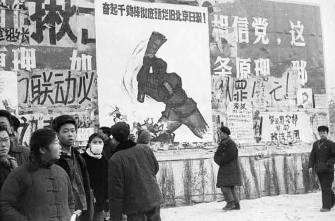 """Un pequeño grupo de jóvenes chinos pasan frente a varios dazibaos (pancartas revolucionarias) en el centro de Beijing en febrero de 1967, durante la """"Gran Revolución Cultural Proletaria"""". Desde que se lanzó la revolución cultural en mayo de 1966 en la Universidad de Beijing, el objetivo de Mao fue reconquistar el poder luego del fracaso del """"Gran Salto Adelante"""". (JEAN VINCENT/AFP/Getty Images)"""