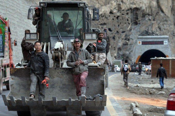 Trabajadores pakistaníes y chinos se sientan en una excavadora al dejar el túnel recién construido en el Valle Gojal de Pakistán, el 25 de septiembre de 2015. El proyecto es parte de la ambiciosa iniciativa de China, 'Un cinturón, Un camino'. (Aamir Qureshi/AFP/Getty Images)