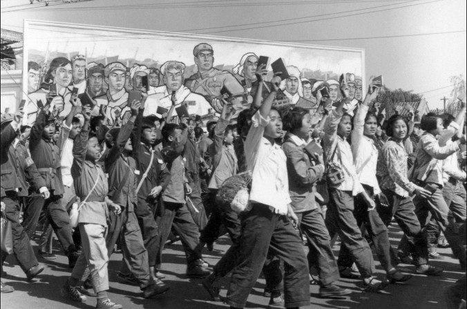 """Estudiantes chinos universitarios y de secundaria de los Guardias Rojos llevando copias del """"Pequeño libro rojo"""" de Mao Zedong mientras desfilan en las calles de Beijing al comienzo de la Revolución Cultural en junio de 1966. Durante la Revolución Cultural (1966-1976), bajo la dirección de Mao, los Guardias Rojos iban descontrolados por todo el país, humillando, torturando y matando a los que percibían como enemigos de clase, y hurtando símbolos culturales que se considerasen que no eran representativos de la revolución comunista. (Jean Vincent/AFP/Getty Images)"""