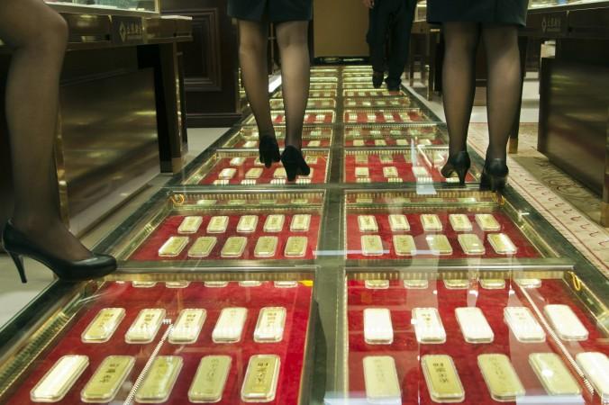 Personal de ventas chino camina a lo largo de un pasillo hecho de lingotes de oro en una casa de intercambio de oro en Kunming, China, el 11 de diciembre de 2012. (STR/AFP/Getty Images)