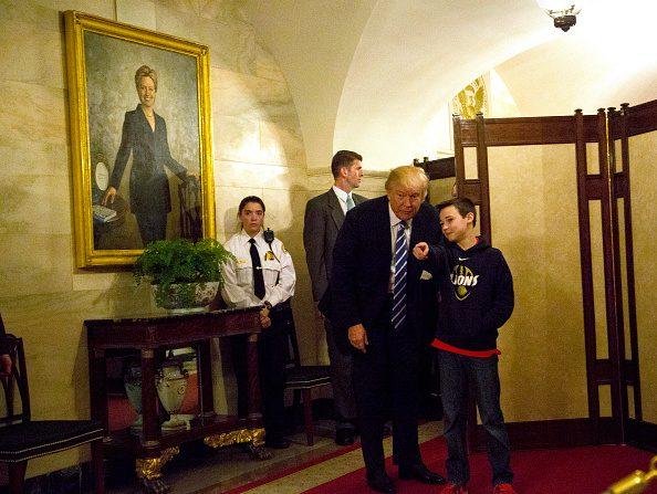El presidente estadounidense Donald Trump saluda a Jack Cornish (10), en un pasillo de la Casa Blanca, delante de un retrato de Hillary Clinton el 7 de marzo de 2017, en Washington DC. (Aude Guerrucci-Pool / Getty Images)