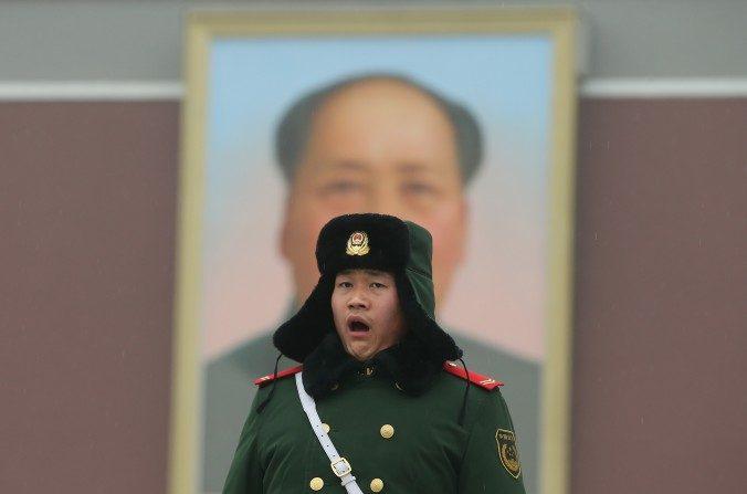 Un policía hace guardia en frente de un enorme retrato del difunto presidente Mao Zedong en la Plaza de Tiananmén en 2013 en Beijing, China. (Feng Li/Getty Images)